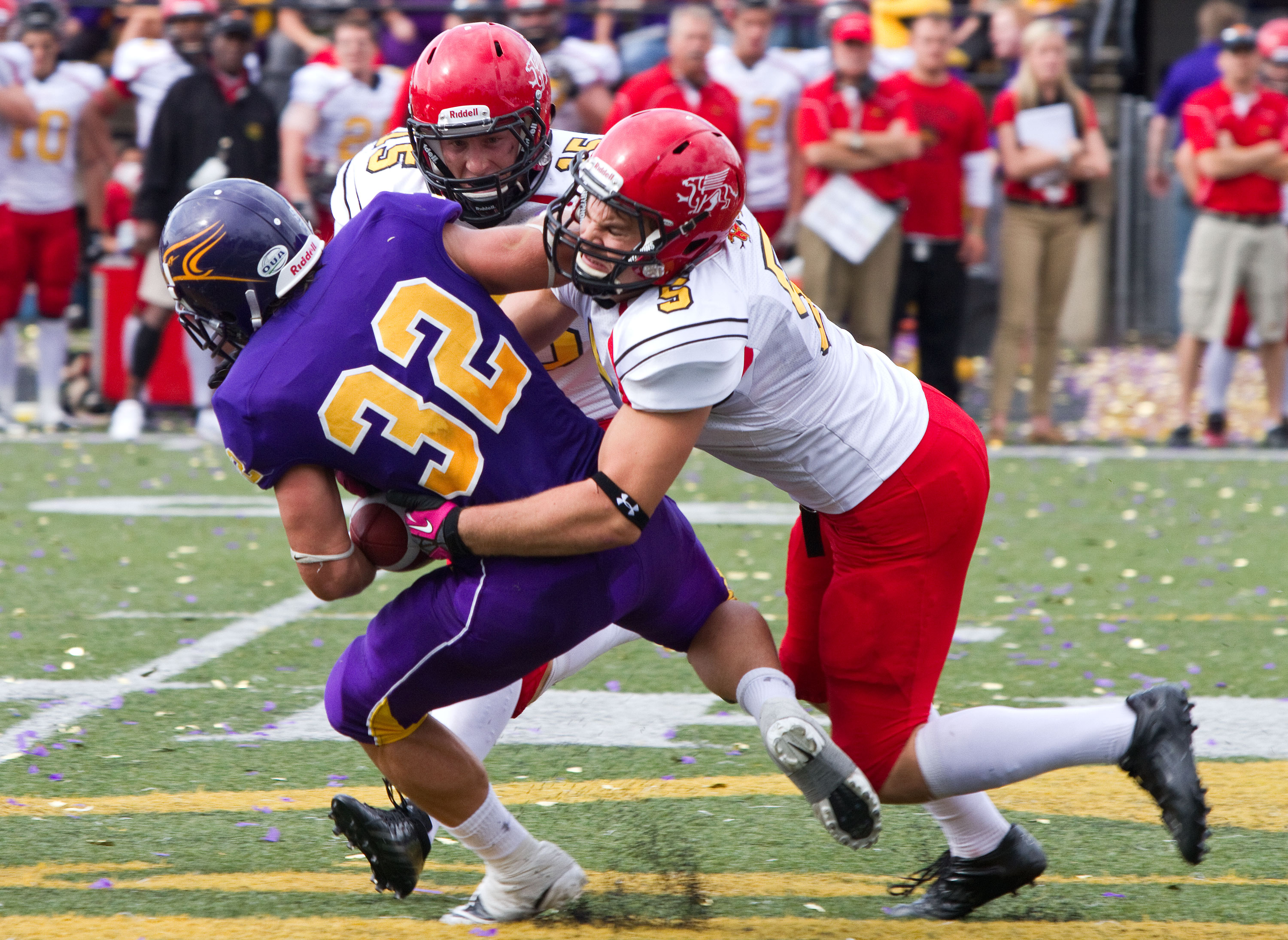 Laurier's Josh Pirie is swarmed by a pair of Gryphons. (Photo by Nick Lachance).