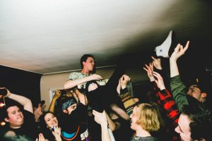 Lukas Foote of Fighting Season keeps pace while suspended in a crowd surf.