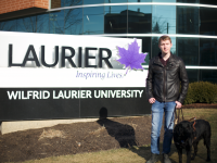 Jack McCormick with his service guide dog, Jake, beside a Laurier sign